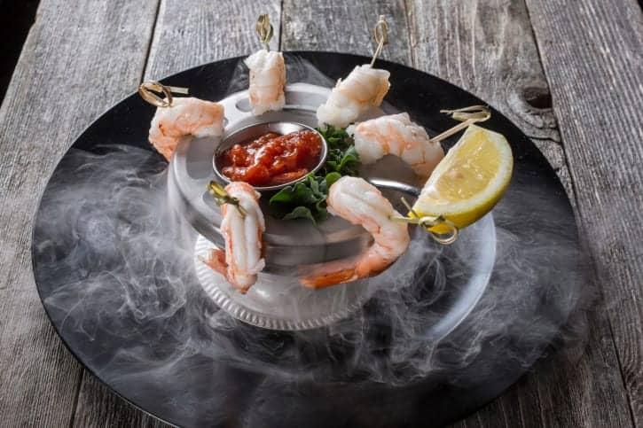 Gourmet smoking shrimp cocktail served on dry ice with lemon used at Icemakergeeks.com